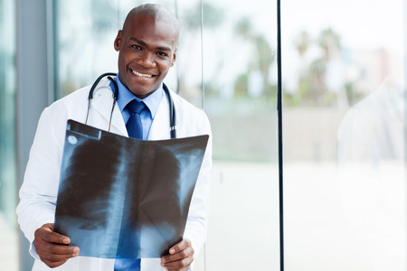 happy african american medical worker holding patients x-ray in office photo