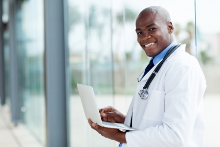 portrait of afro american doctor using laptop computer photo