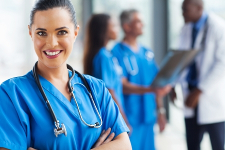 nurse uniform: smiling young doctor looking at the camera with colleagues  Stock Photo