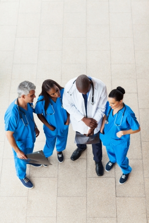 overhead view of doctors looking at patient's x-ray photo