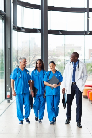 group of professional health care workers walking in hospital photo