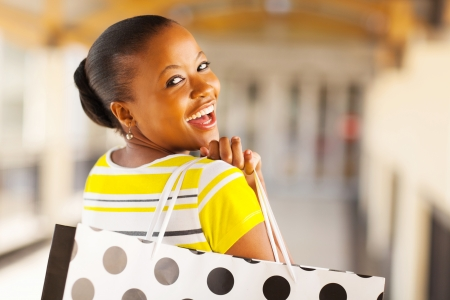 cheerful african young lady in shopping mall photo
