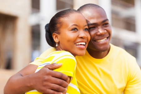 afro woman: happy young african american couple outdoors looking away