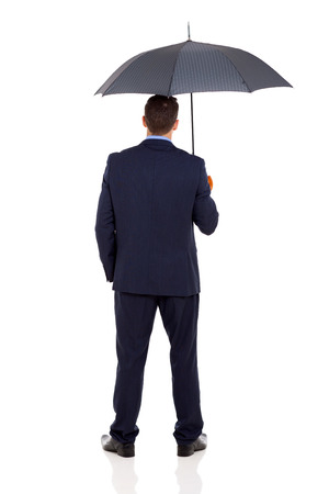 rear view of businessman with an umbrella on white  photo