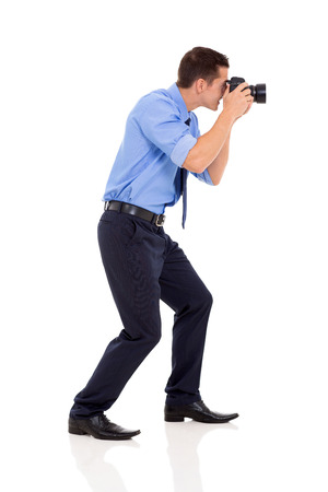 side view of male photographer taking photos on white background photo