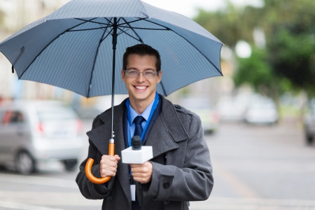 live work city: male news reporter holding umbrella and live broadcasting in the rain Stock Photo
