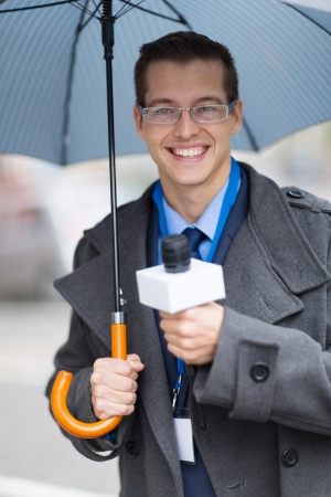live work city: handsome young journalist working outdoors in the rain Stock Photo