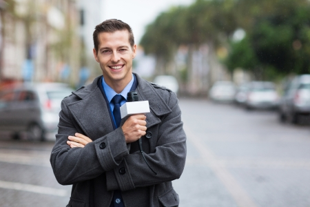 weather report: confident young news reporter working outdoors in the rain