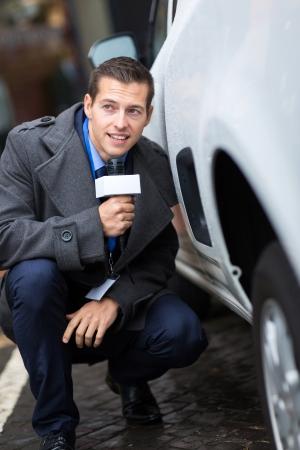 reportero: paparazzi escondido detrás de un coche Foto de archivo