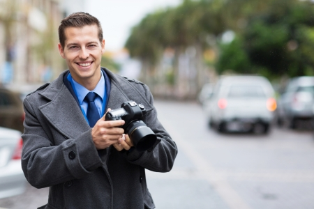 handsome journalist holding a camera in the city in the rain photo