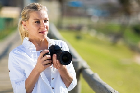 thoughtful middle aged female photographer holding camera outdoors photo