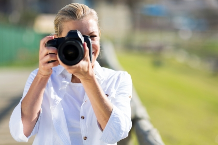 dslr camera: mature female photographer taking photos outdoors