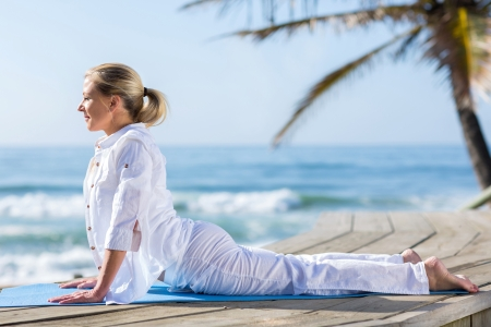 peaceful middle aged woman practice yoga on beach Stock Photo