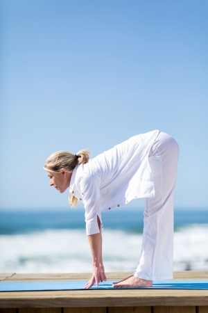healthy senior woman stretching on beach photo