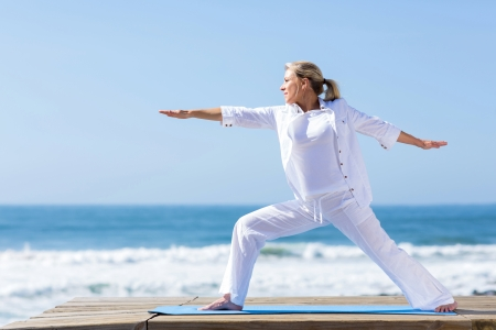 senior adult: mature woman yoga exercise on beach