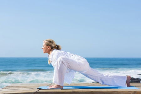 side view of senior woman working out at the beach photo
