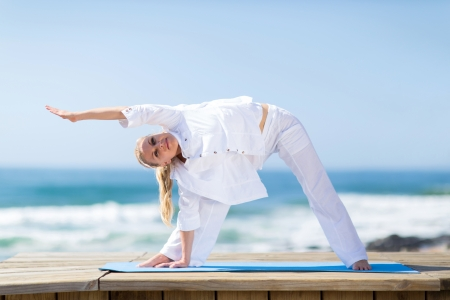 active woman: portrait of fitness senior woman exercising outdoors on beach Stock Photo