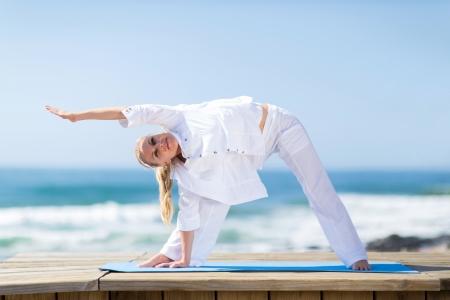 yoga outside: portrait of fitness senior woman exercising outdoors on beach Stock Photo