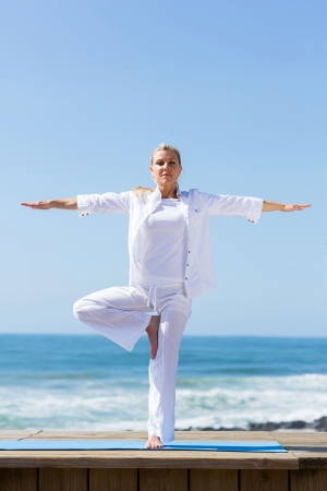 healthy mature woman doing yoga by the beach photo
