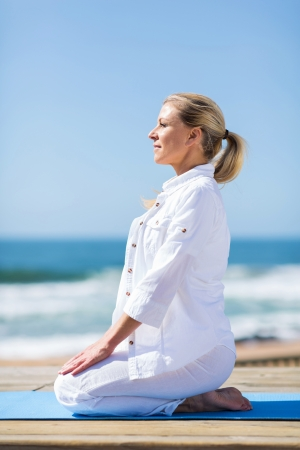 beautiful middle aged woman: beautiful middle aged woman doing yoga on beach Stock Photo