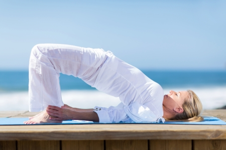 peaceful senior woman exercising yoga outdoors on beach photo