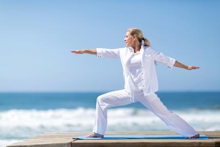 jolie femme d'âge moyen pose de yoga sur la plage