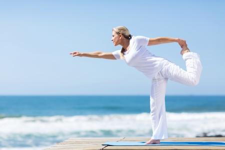 ビーチでヨガを行使して白のフィットの中年女
