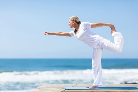 fit middle aged woman in white doing yoga exercise at the beach
