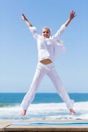 carefree active senior woman jumping on beach photo
