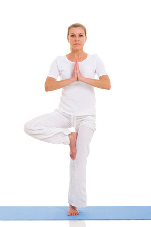 portrait of mature woman doing yoga exercise on white  photo