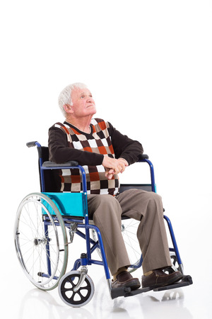 thoughtful senior man on a wheelchair looking up isolated on white photo