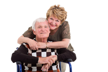 senior citizen woman: supportive elderly wife hugging handicapped husband isolated on white Stock Photo