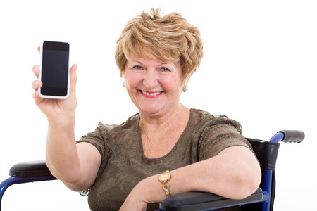 pretty elderly woman in a wheelchair showing a smart phone on white background photo