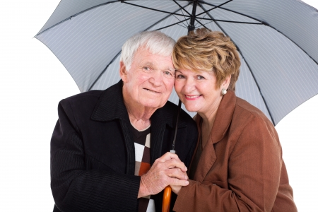 cute senior husband and wife under an umbrella on white photo