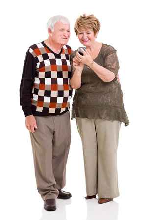 lovely senior couple using smart phone on white background photo