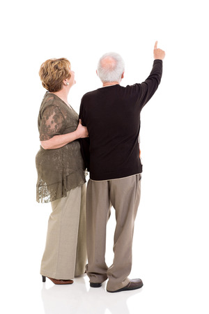senior citizen woman: rear view of senior couple pointing at copy space on white background