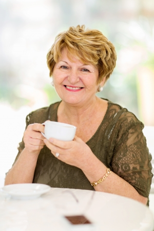 happy mature woman drinking coffee at home photo
