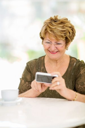 home phone: happy elderly woman reading emails on smart phone at home