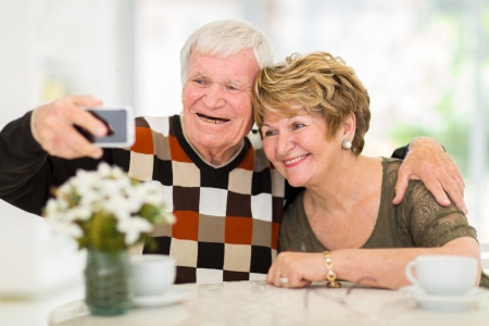 cheerful senior couple using cell phone at home photo