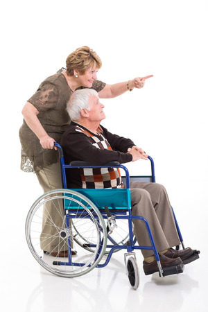 cheerful senior woman pointing while her disabled husband on wheel chair photo
