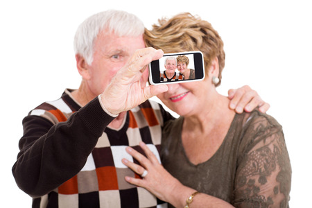 happy senior couple taking self portrait with smart phone isolated on white photo