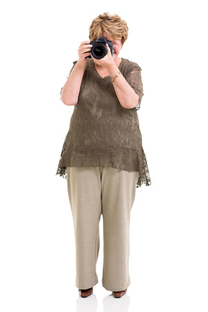 elderly woman shooting pictures with digital SLR camera on white photo