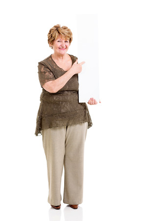 cheerful elderly woman pointing at empty white board isolated on white photo