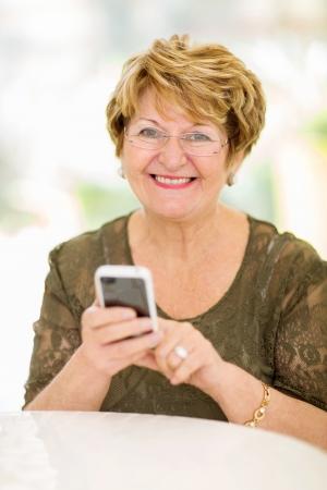 persona de la tercera edad: mujer alegre de alto nivel utilizando tel�fono inteligente en el hogar