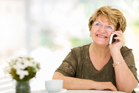 pretty senior woman talking on her cell phone at home Stock Photo