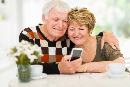 lovely elderly couple using smart phone at home photo