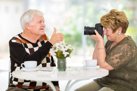 taking a wife: senior wife taking a photo of her husband with digital SLR camera Stock Photo