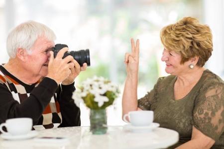 hombre disparando: hombre mayor fotografiar a su esposa con una cámara digital Foto de archivo