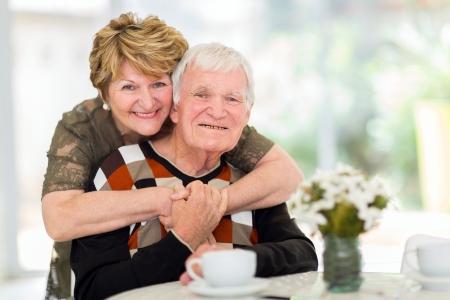 retirement homes: lovely retired elderly couple hugging at home