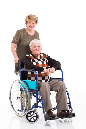 disabled old man sitting on wheelchair with caring wife on white background photo